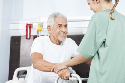 female nurse helping smiling senior men in using walker